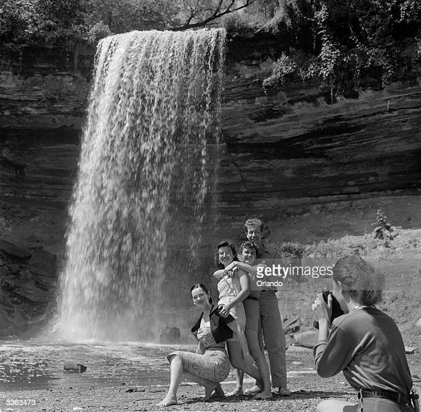 Group of AYH members on a cycling trip out of Minneapolis, Minnesota, stop for a photograph against a dramatic backdrop. Behind them Minnehaha Creek,...