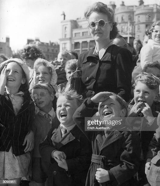 A group of children enjoying a Punch and Judy show in Brighton with their mothers