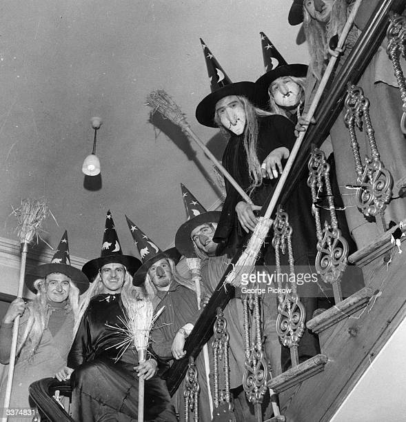 Group of men in costume as witches, complete with brooms, to celebrate Halloween, line the staircase of a house.