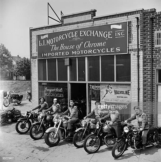 Group of women dubbed the 'Motor Maids of America' sit astride their motorcycles outside the shop they use as their headquarters.
