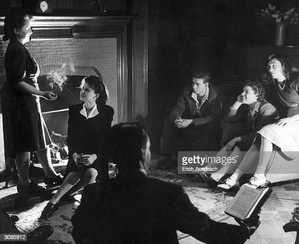 A group of young people sit around a fireplace in a Harrow home reading talking and smoking