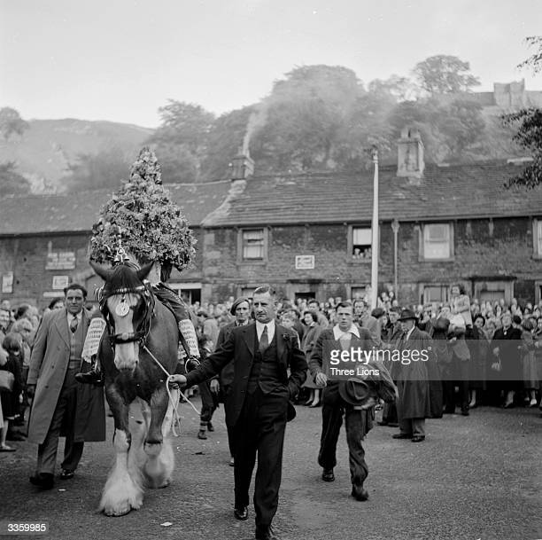 A horse cowned with a giant headdress made from branches flowers and leaves leads a procession through the streets of Castleton Derbyshire to mark...