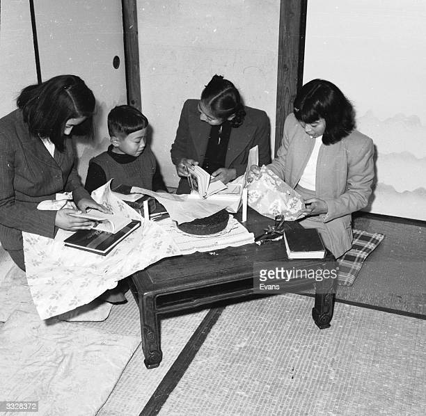 A Japanese family kneel round a low table opening Christmas presents