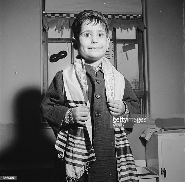 A Jewish boy wearing his tallith as a sign of devotion to God during his weekday morning prayers