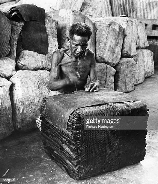 A labourer arranges raw rubber into bales ready for export from Portuguese Timor