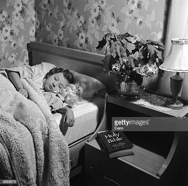A little girl sleeps peacefully in bed her doll by her side A bible rests on her bedside table