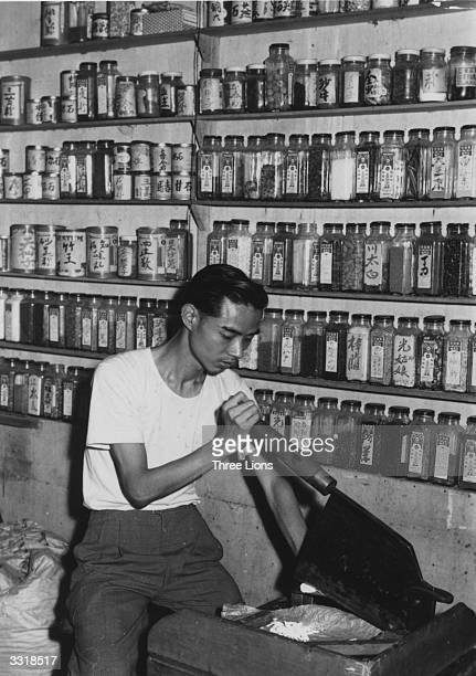 A man in Hong Kong uses a large chopper to slice up root herbs The bottles of the shelves behind him contain herbs in powder form
