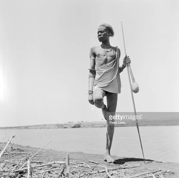 A man of the Nuer tribe standing in the typical rest position of his tribe holding a spear