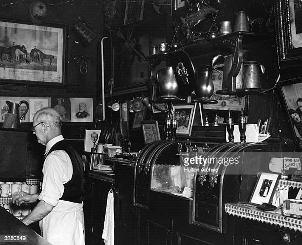 A man stands behind a counter and reaches for a mug