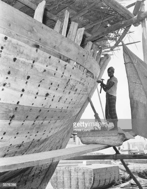 A man working on a large wooden boat at a shipyard in Manama Bahrain