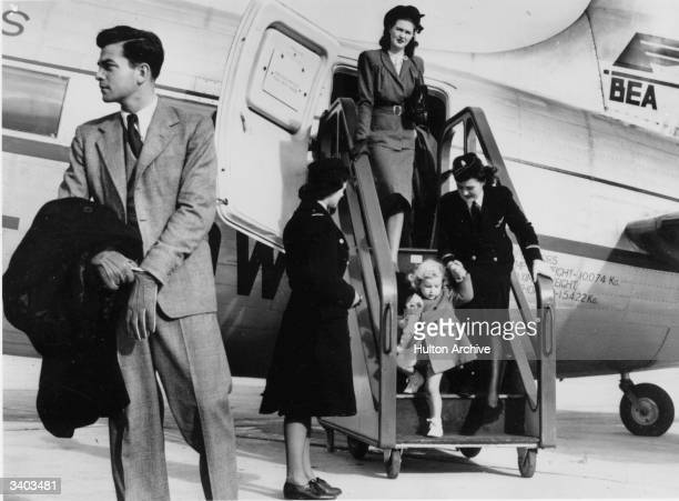 A mother and child being helped by air stewardesses as they disembark from a BEA Vickers Viking