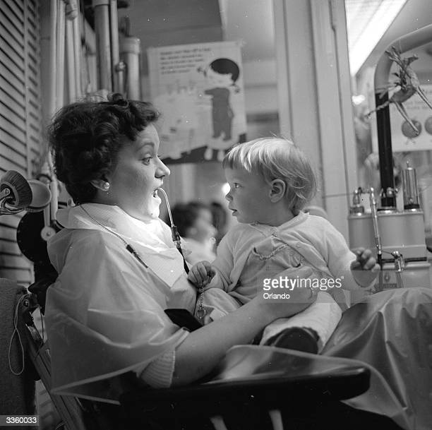A mother sits in the dentist's chair with her young daughter on her knee