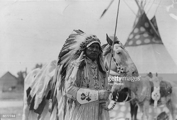 A native North American in headress in front of a teepee