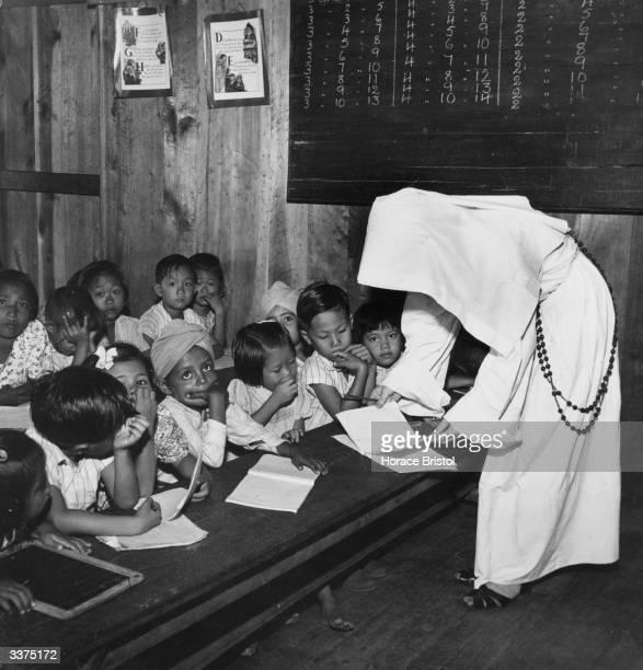 A nun teaching a group of infant school children