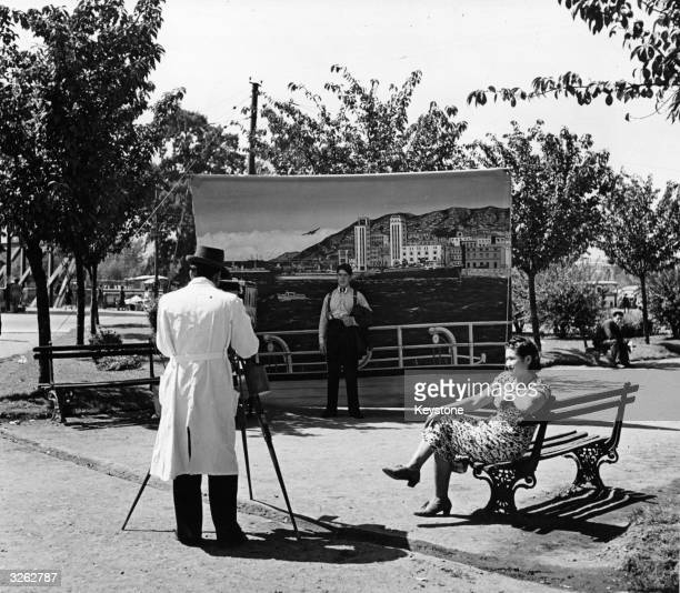 A photographer in a Santiago park sets up a backdrop in order to give the impression that his subject is on a liner at sea