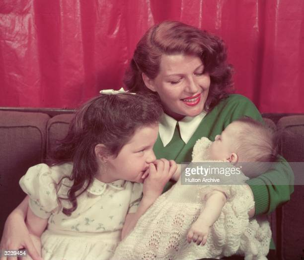 A portrait of American actor Rita Hayworth sitting on a sofa with her young daughters Rebecca Welles and Yasmin Khan in her lap Hayworth is wearing a...