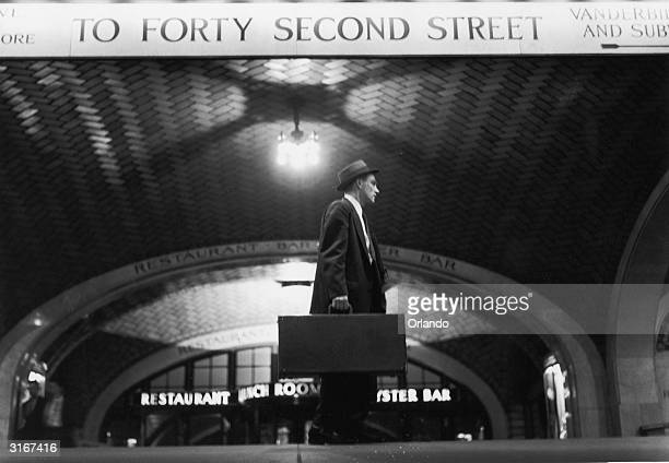 Salesman arriving at Grand Central Station, New York, makes his way towards 42nd Street.
