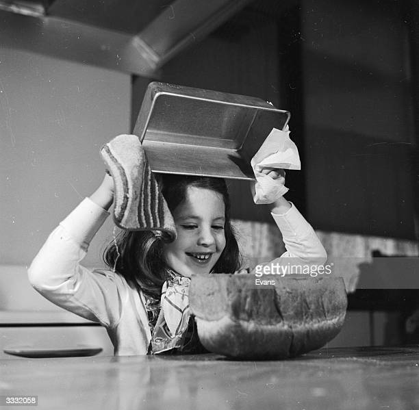 A schoolgirl removes a freshly baked loaf from a baking tray