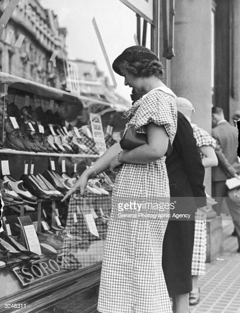 Shopper spots a bargain in the window of a Sorosis shoe shop.