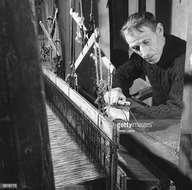 A weaver at work at a loom on the Aran Islands in County Galway The woven cloth is wound on under his forearms