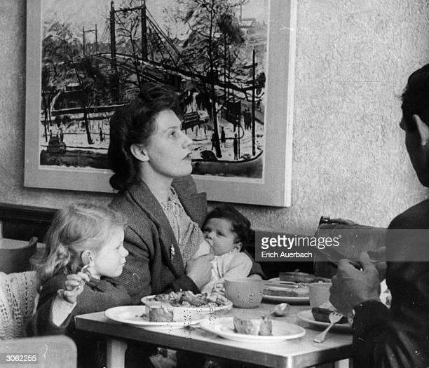 Woman feeding her baby in a London teashop.
