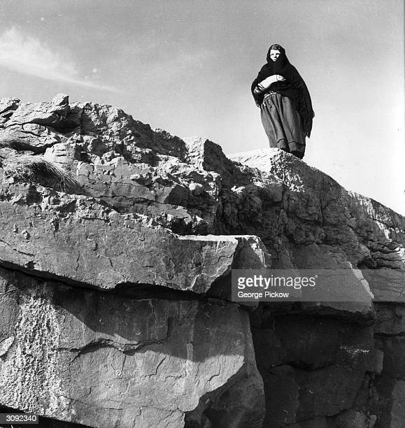A woman gazes towards the mainland from the Aran Islands in the mouth of Galway Bay County Galway