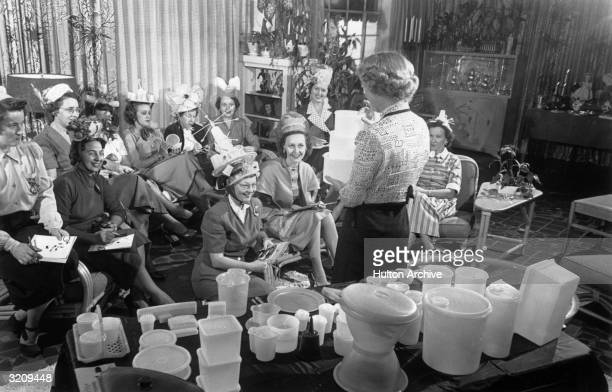 A woman holds three Tupperware containers while standing in front of a group of women seated in a living room during a Tupperware party Some of the...