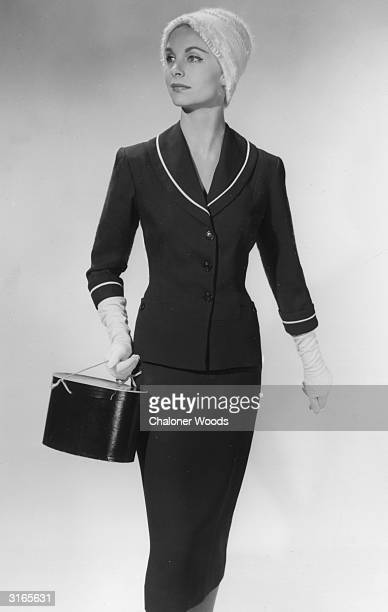 A woman modelling a Kay Bee tailored suit with white piping at the collar and cuffs