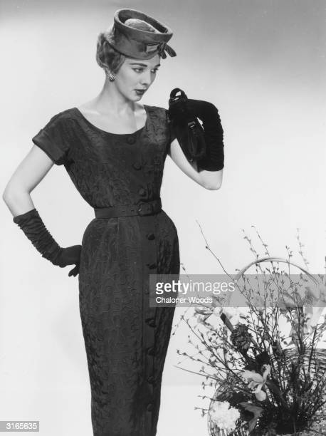 A woman modelling an elegant shortsleeved dress in a dark fabric with decorative embroidery and buttons down the front