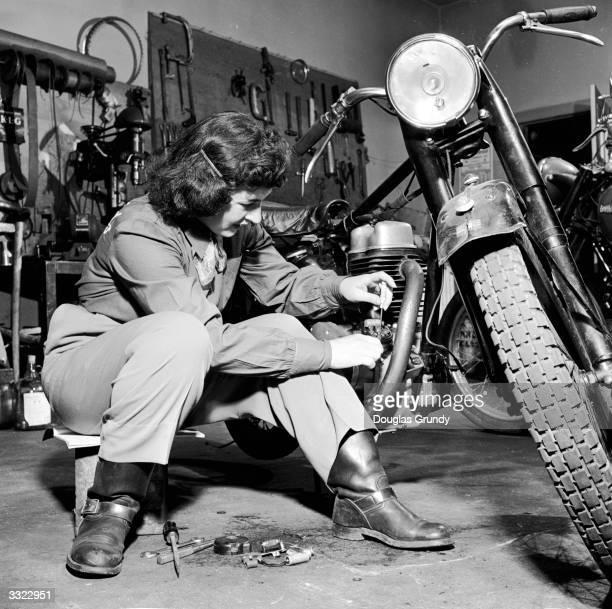 Woman repairing her motorbike inside a workshop.