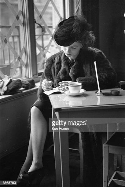 A woman sitting in a cafe alone with her notebook and a cup of coffee Original Publication Picture Post 961 Idle Women unpub