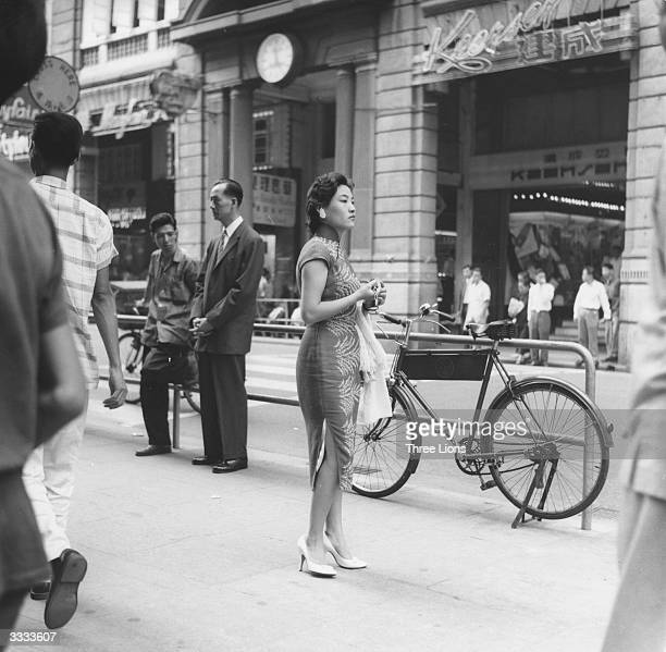 A woman standing on busy street in Victoria Hong Kong