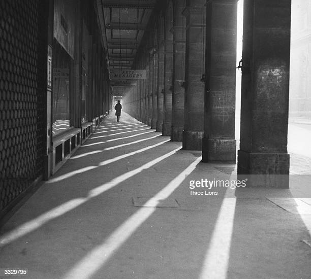 A woman walks beside the large pillars of the arcade at the western end of the Rue Rivoli Paris