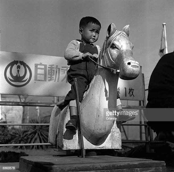 A young boy looks uncomfortable on a mechanised horse at the funfair on top of the Takashimaya department store in Tokyo