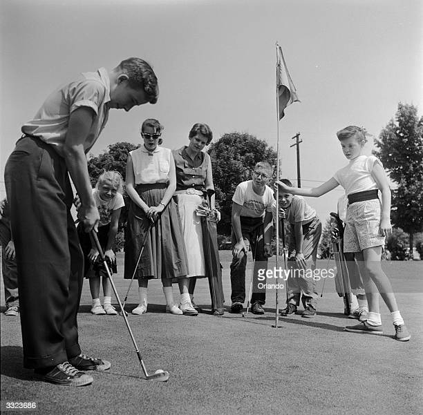 A young golfer lines up a putt at the Hershey Juvenile golf club Pennysylvania