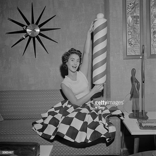 A young woman demonstrates a novelty cushion in the shape of a barbershop sign
