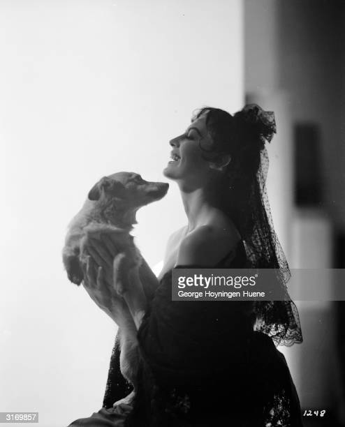 Actress Ava Gardner lavishes affection on a small dog.
