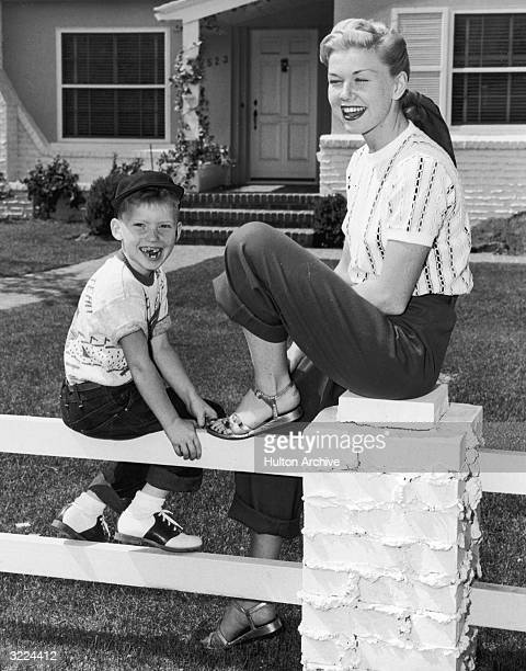American actor and singer Doris Day smiles and laughs as she sits on a fence in front of a house with her son Terry Day wears sandals trousers and...