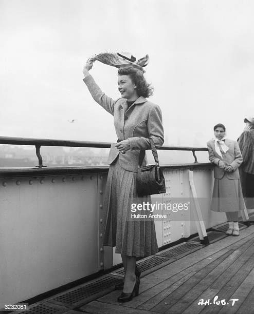American actor Jane Wyman waves her scarf from the deck of a ship upon returning from England where she filmed director Alfred Hitchcock's film...