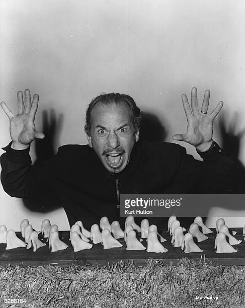 American actor Jose Ferrer star of the United Artists film 'Cyrano De Bergerac' surrounded by a collection of outsized prosthetic noses The film was...