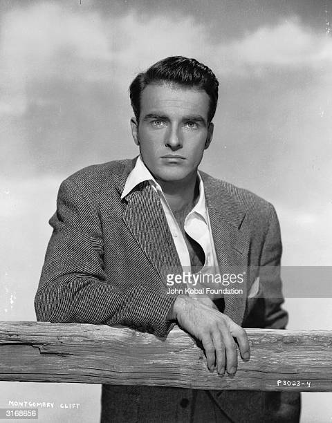 American actor Montgomery Clift leaning on a fence with an intent expression