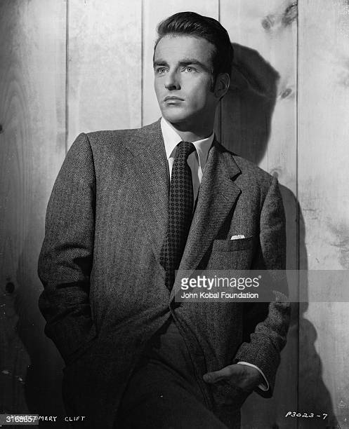 American actor Montgomery Clift lounges against a fence in a smart suit