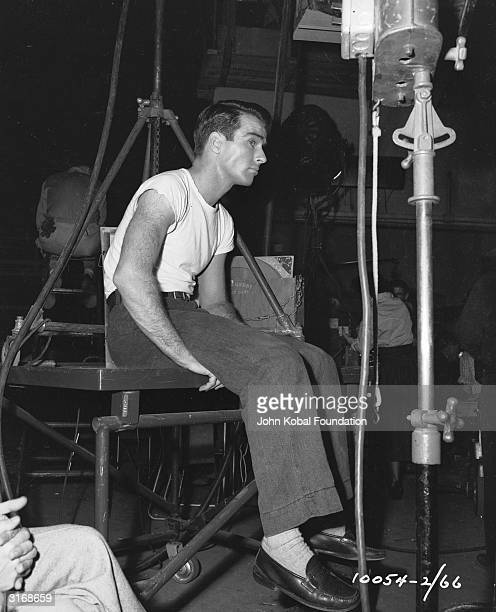 American actor Montgomery Clift sitting amidst a clutter of studio equipment on the set of 'A Place in the Sun'