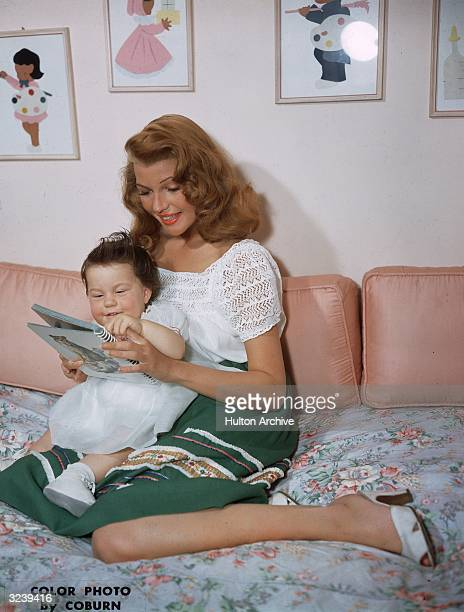 American actor Rita Hayworth looks through an illustrated book with her infant daughter Rebecca Welles as she holds her in her lap while sitting on a...