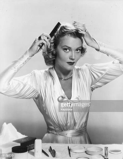 American actress and the wife of wayward actor Errol Flynn, Patrice Wymore combing her hair.