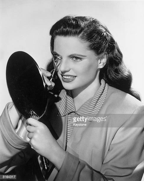American actress Geraldine Brooks using an eyelash curler