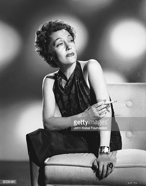 American actress Gloria Swanson smoking a cigarette