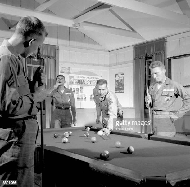 American Airforce Captain Charles Meek plays a game of billiards with other members of Fort Benning's 508th Regimental Combat Team during a rest...