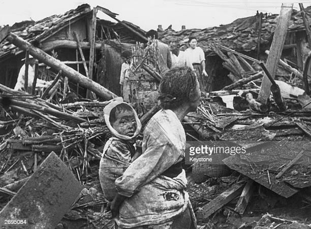 An elderly woman and her grandchild wander among the debris of their wrecked home in the aftermath of an air raid by U.S. Planes over Pyongyang, the...