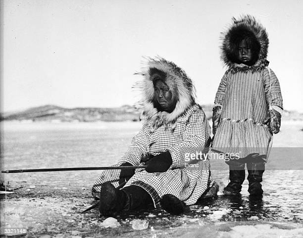An Inuit woman and her daughter fish through a hole on an icy expanse in Alaska.